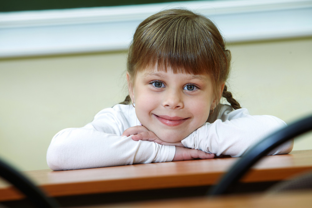 Portrait Of Smart Schoolgirl Looking At Camera With Smile