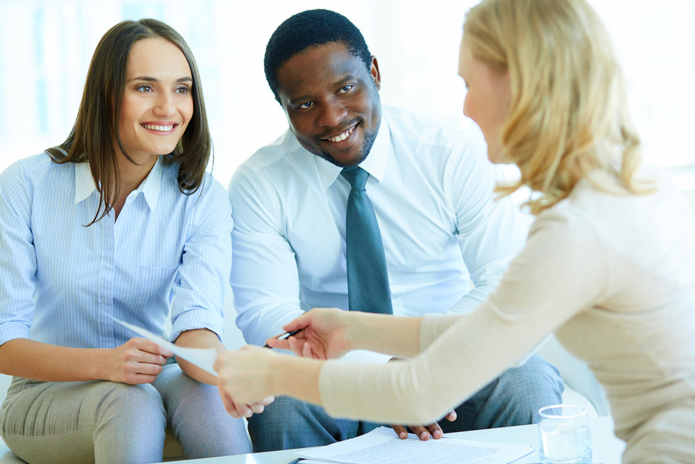Young Businesswoman Giving Paper And Pen To Smiling Female At Meeting