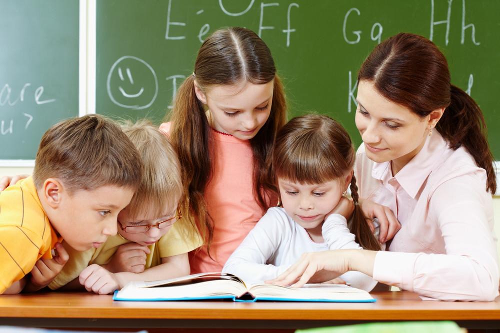 Portrait Of Smart Schoolchildren And Their Teacher Reading Book In Classroom
