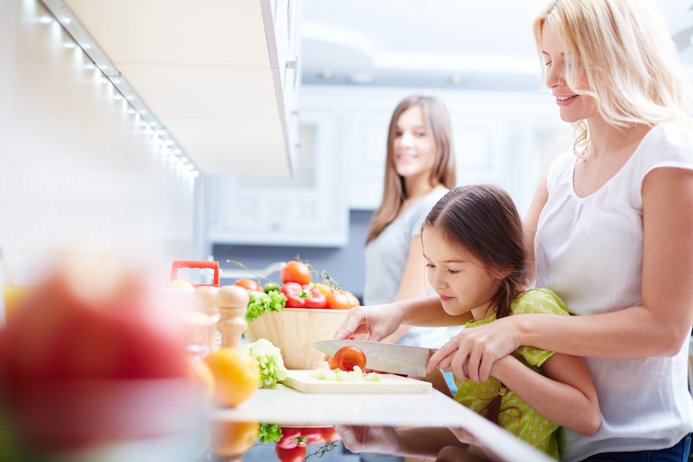 Portrait Of Happy Mother And Two Daughters Cooking In The Kitchen