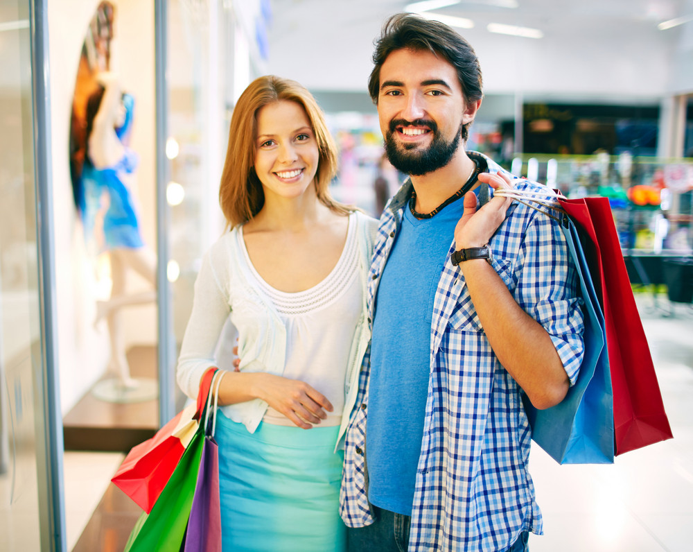 Portrait Of Young Couple Looking At Camera In The Mall