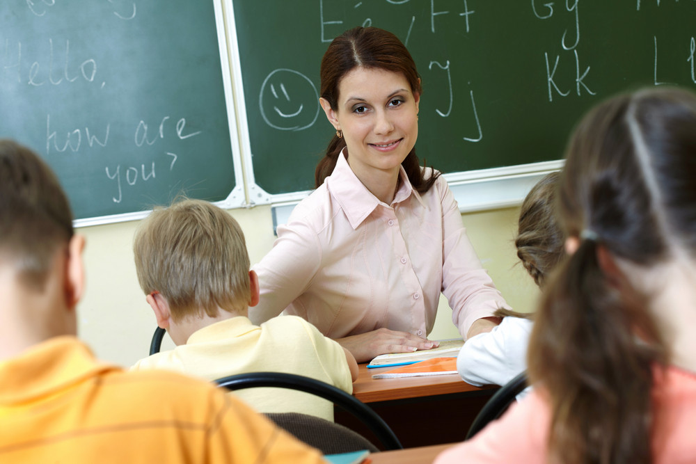 Portrait Of Smart Teacher At Workplace Looking At Schoolkids In Classroom