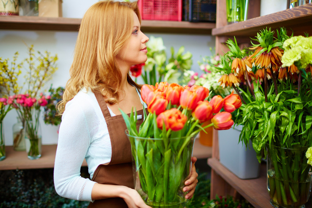 Portrait Of Young Female Florist With Big Vase Of Red Tulips