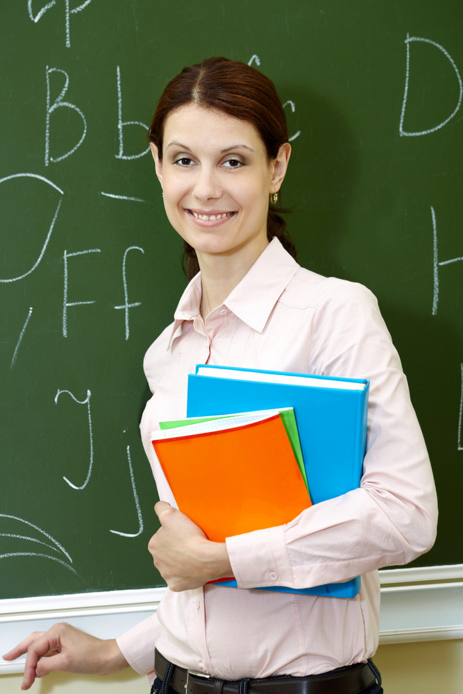 Portrait Of Smart Teacher With Books By The Blackboard Looking At Camera