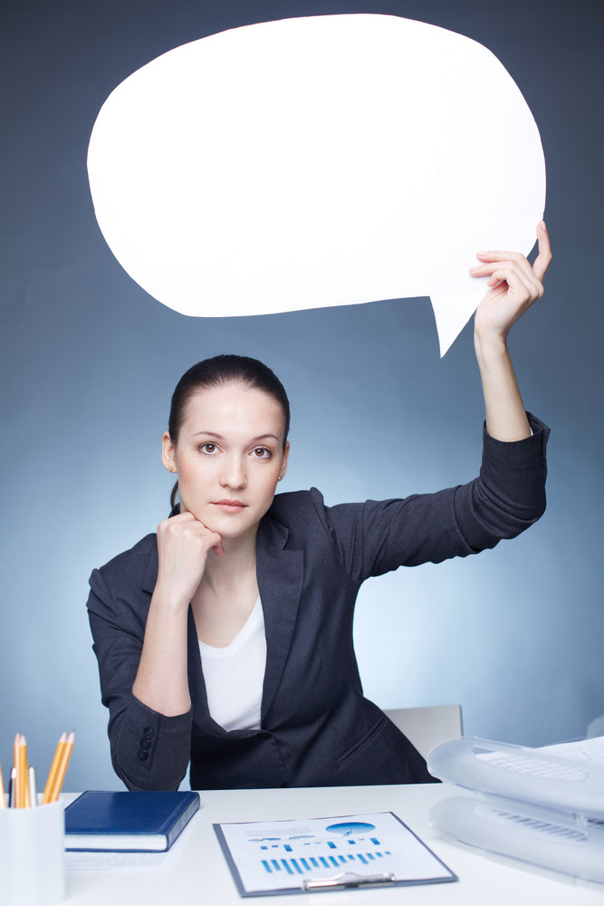 Image Of Serious Businesswoman With Paper Speech Bubble In Her Hand Looking At Camera