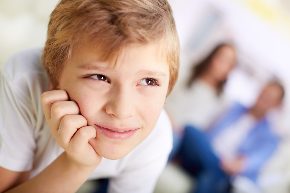 Portrait Of Smiling Boy On Background Of His Parents