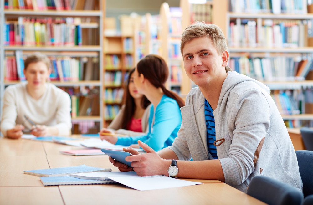 Portrait Of Handsome Student With Touchpad Sitting In College Library