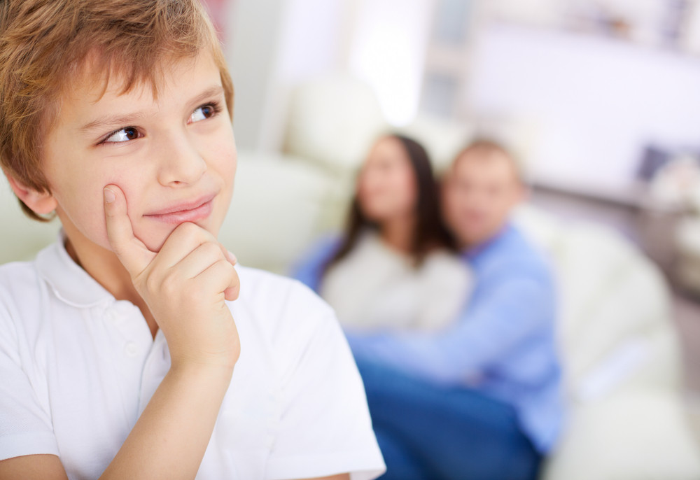 Portrait Of Pensive Boy On Background Of His Embracing Parents