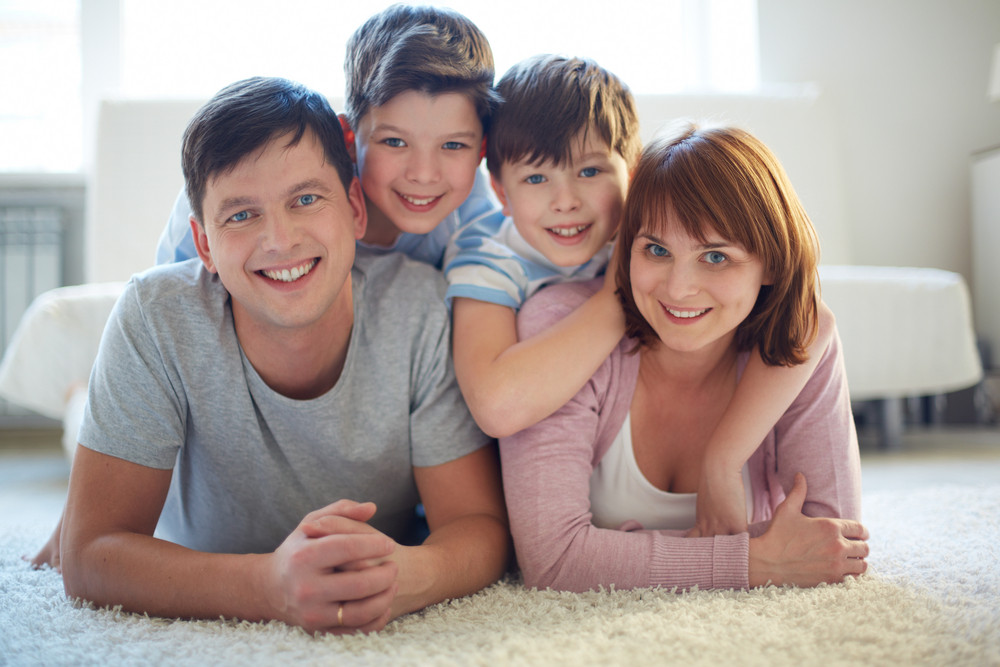Portrait Of Happy Family Of Four Lying On The Floor And Looking At Camera With Smiles