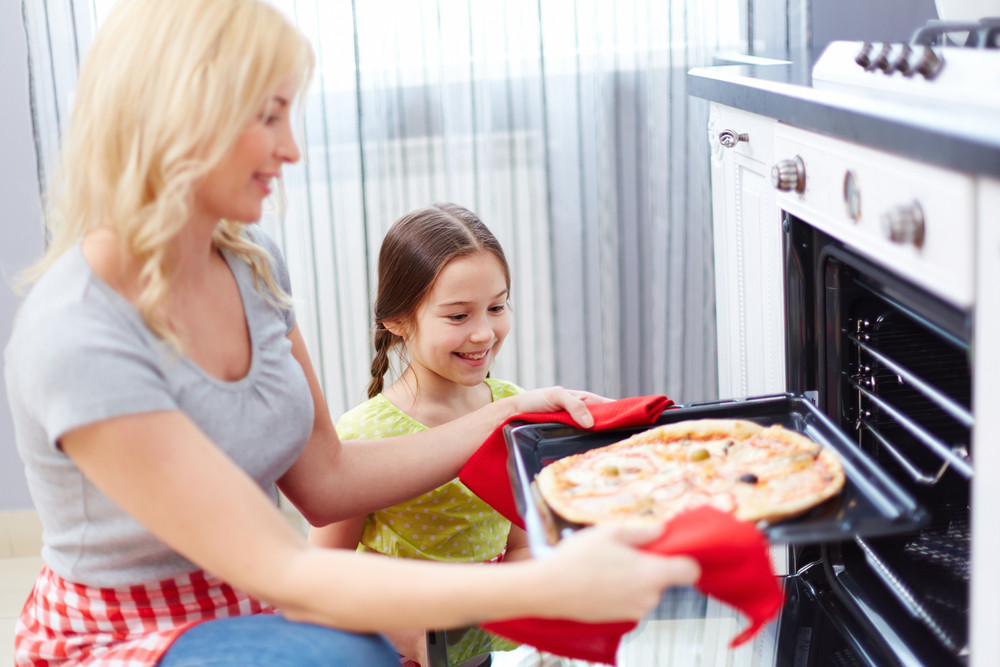 Portrait Of Happy Young Woman Taking Pizza Out Of Oven
