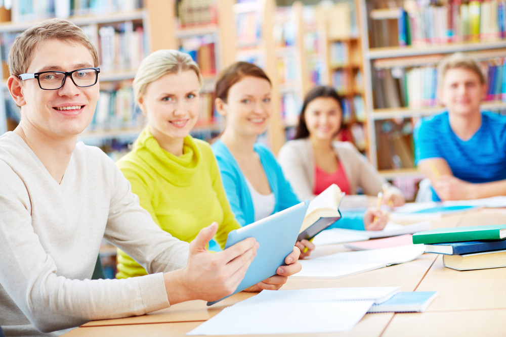 Portrait Of Group Of Students Sitting In College Library