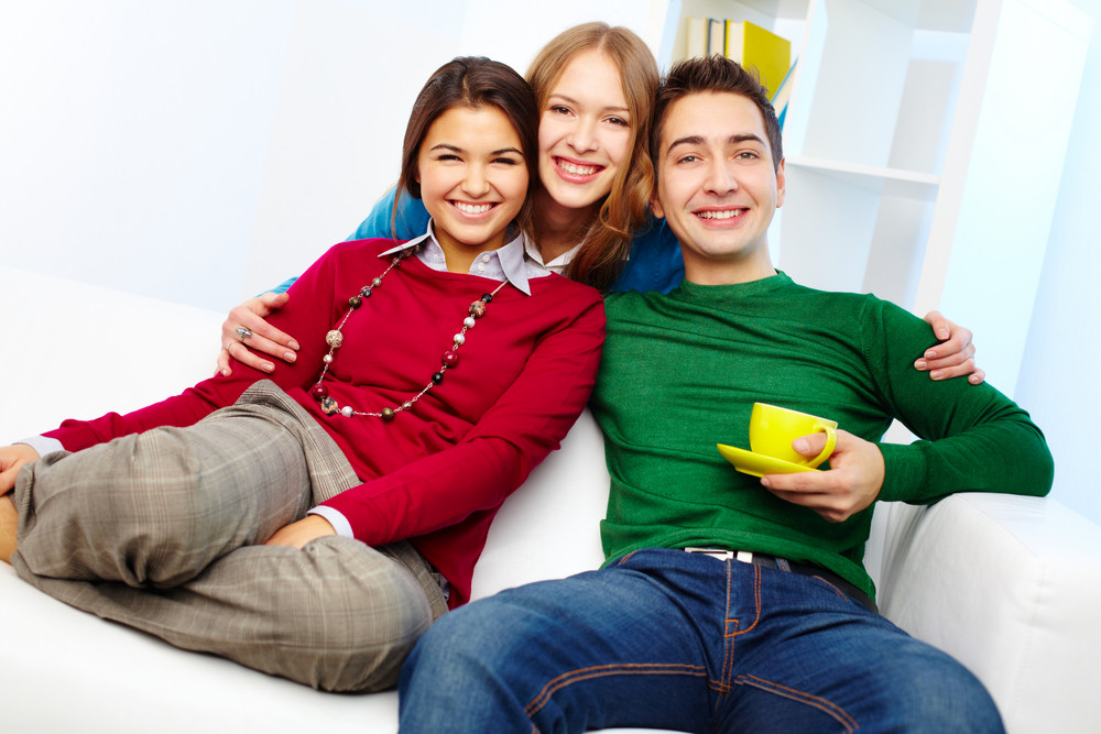 Portrait Of Attractive Friends Looking At Camera While Sitting On Sofa