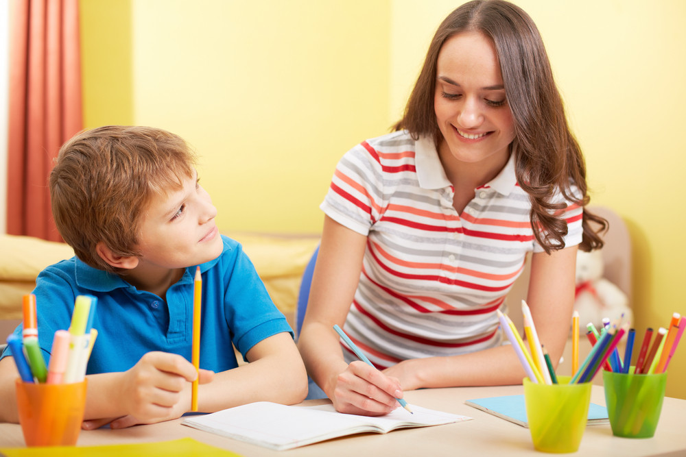 Portrait Of Cute Schoolboy And His Mother Making Schoolwork At Home