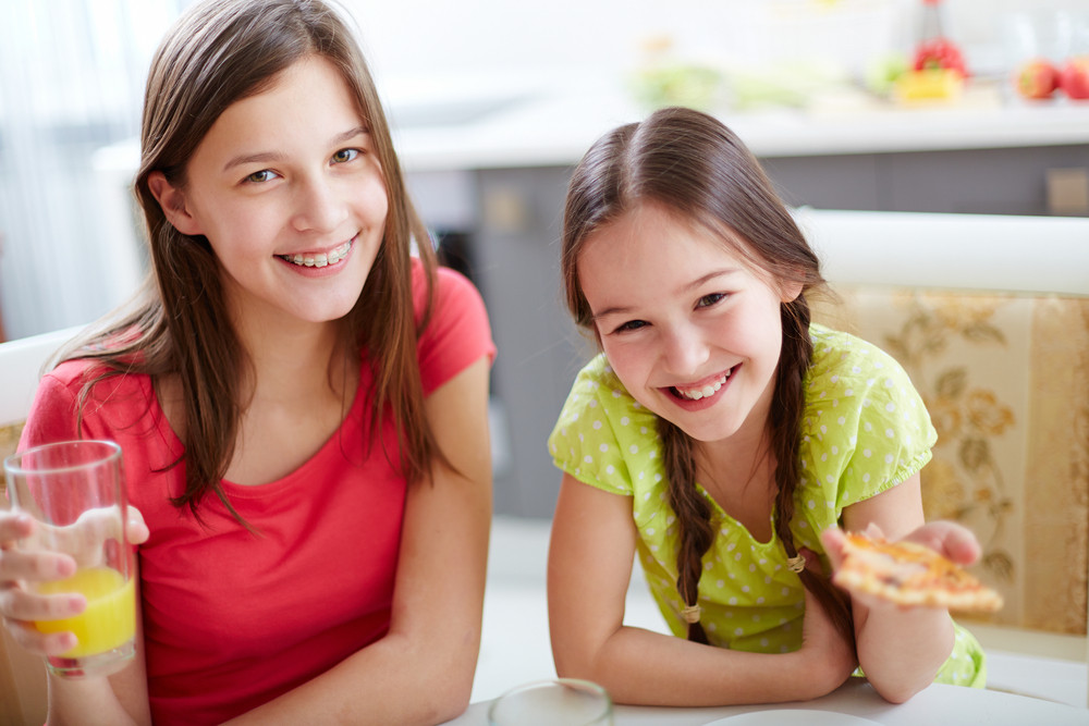 Portrait Of Cute Girls Sitting By Dinner Table And Looking At Camera