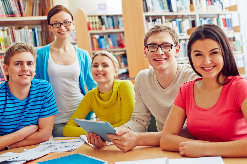 Group Of Friendly Students Looking At Camera In College Library