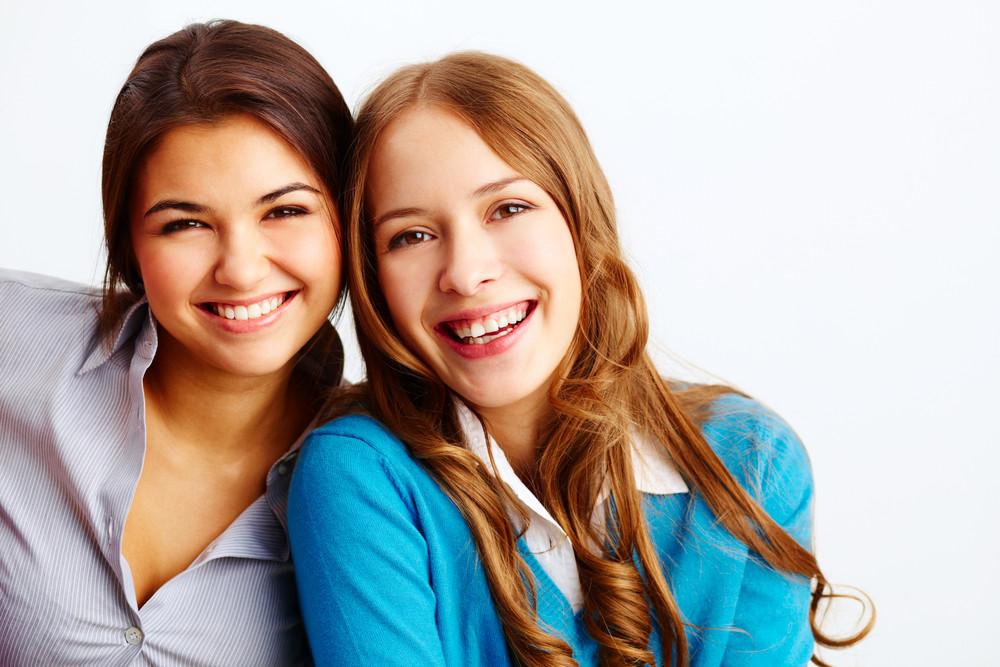 Portrait Of Joyful Girls Looking At Camera On White Background