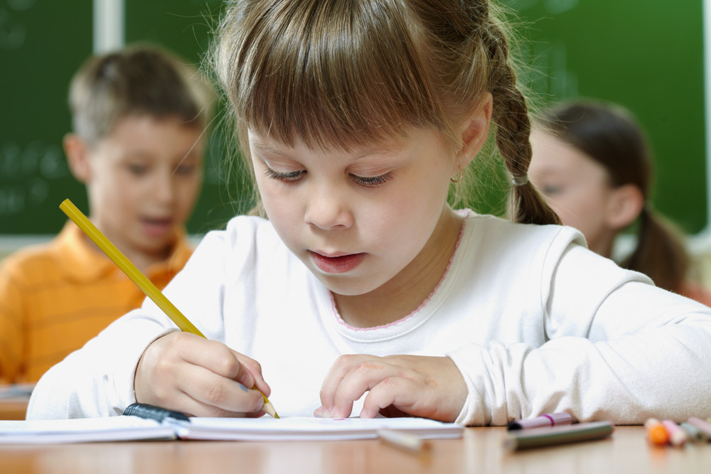 Portrait Of Smart Schoolgirl Drawing At Lesson In Classroom