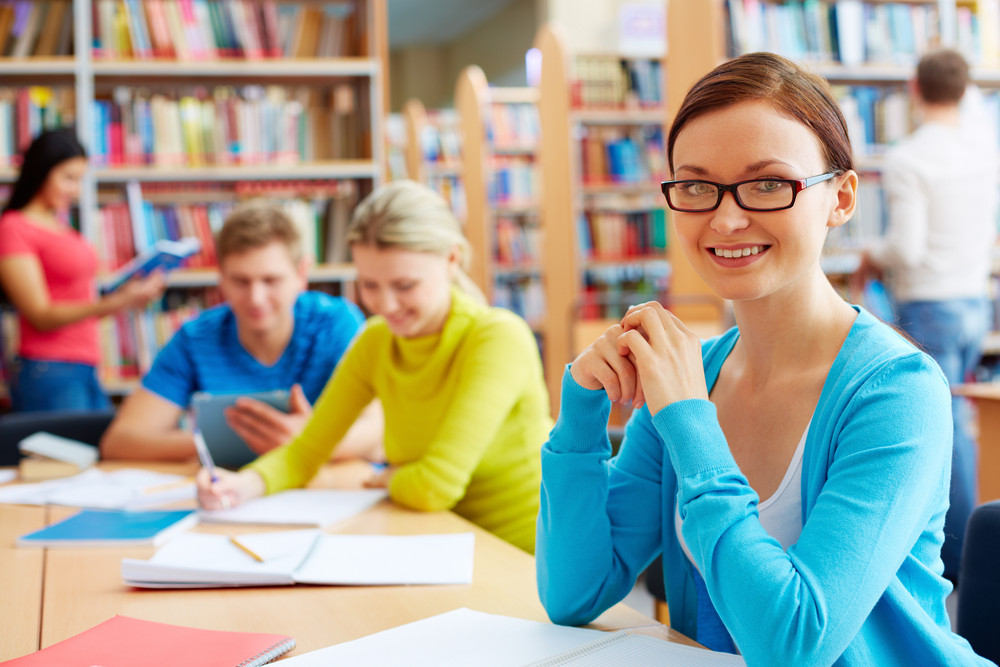 Portrait Of Pretty Girl Sitting In College Library With Her Group Mates On Background