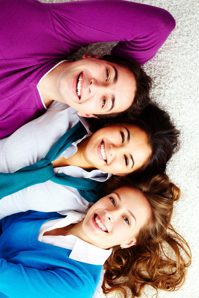 Above Angle Of Three Laughing Friends Lying On The Floor And Looking At Camera