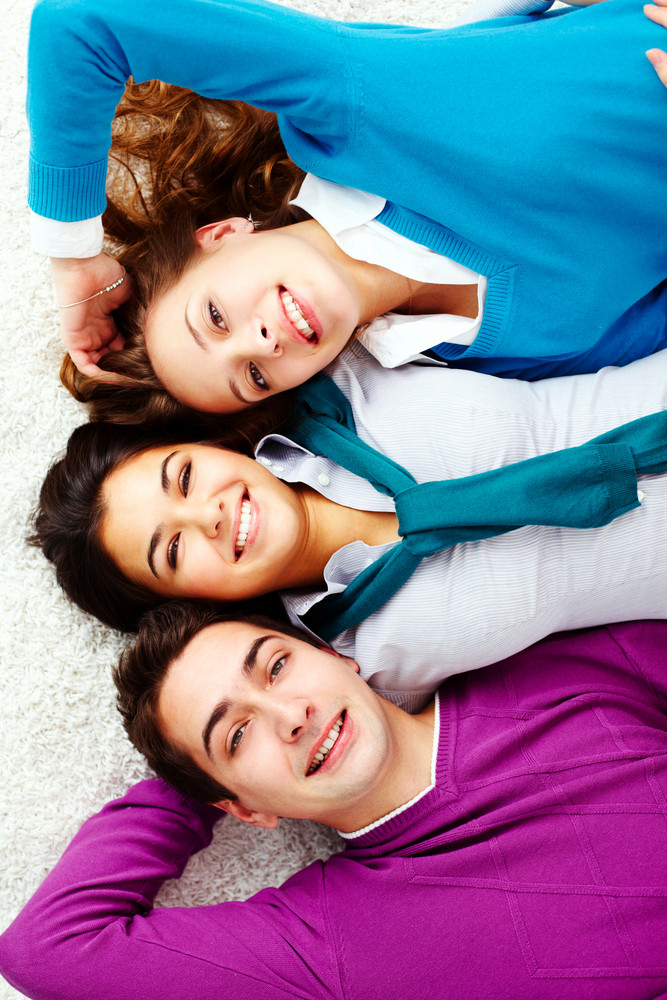 Above Angle Of Three Laughing Friends Looking At Camera And Smiling