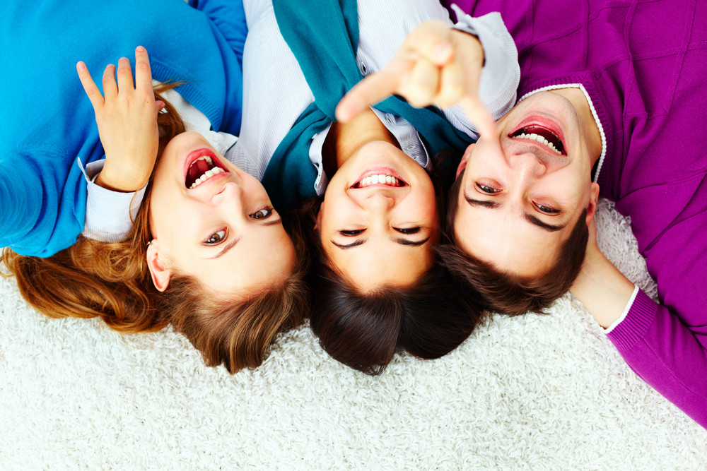 Above Angle Of Ecstatic Friends Looking At Camera