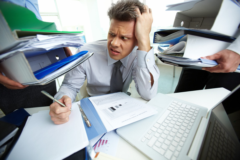 Perplexed Accountant Looking At Huge Piles Of Documents Held By His Business Partners While Doing Financial Reports