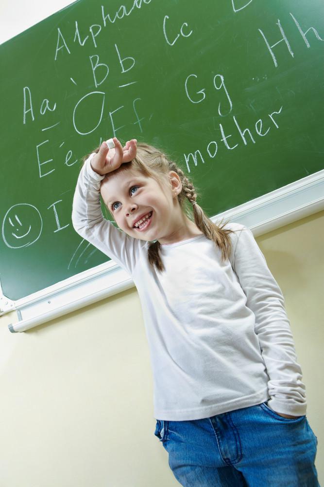 Portrait Of Smart Schoolchild By The Blackboard Laughing