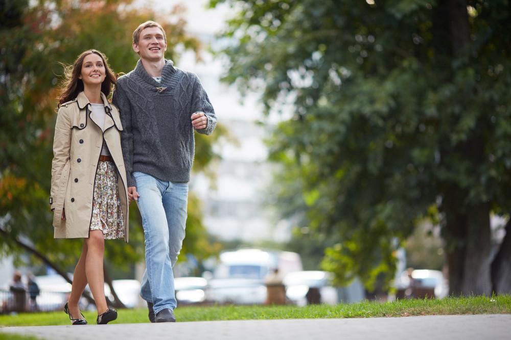 Happy Girl And Her Boyfriend Walking In Park