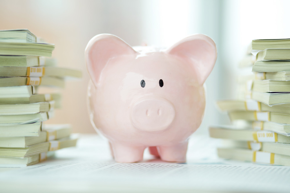 Image Of Pink Piggy Bank Surrounded By Stacks Of Dollar Bills