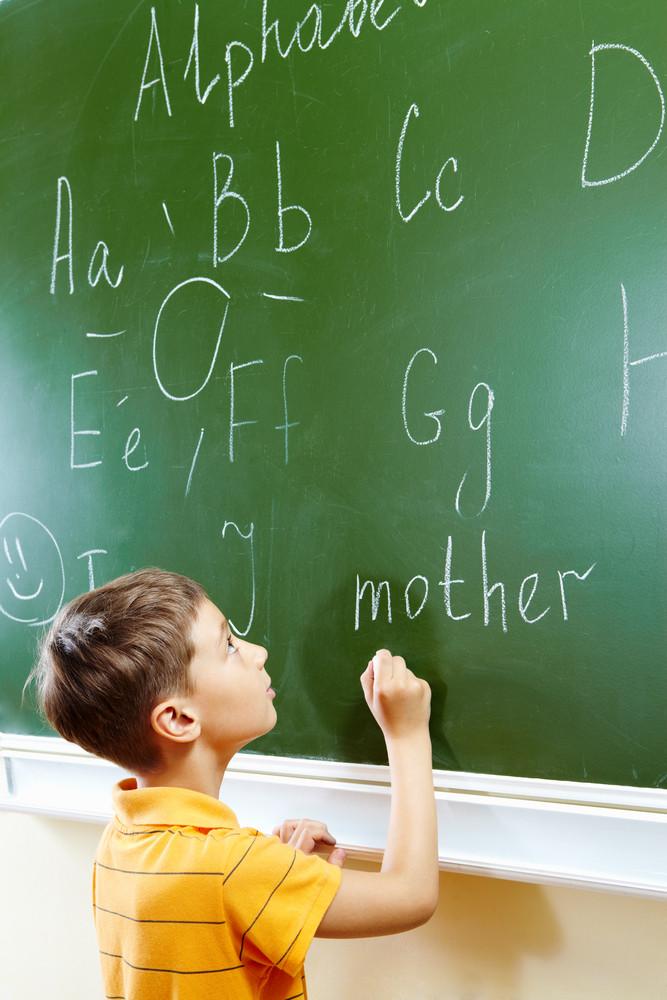 Portrait Of Smart Schoolchild By The Blackboard Looking At It