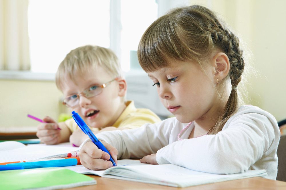 Portrait Of Smart Schoolkids Drawing At Lesson In Classroom