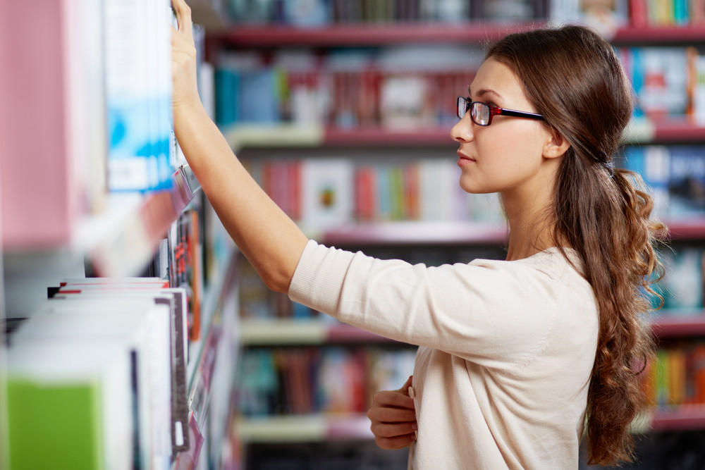 Portrait Of Serious Girl In Library Looking For A Book