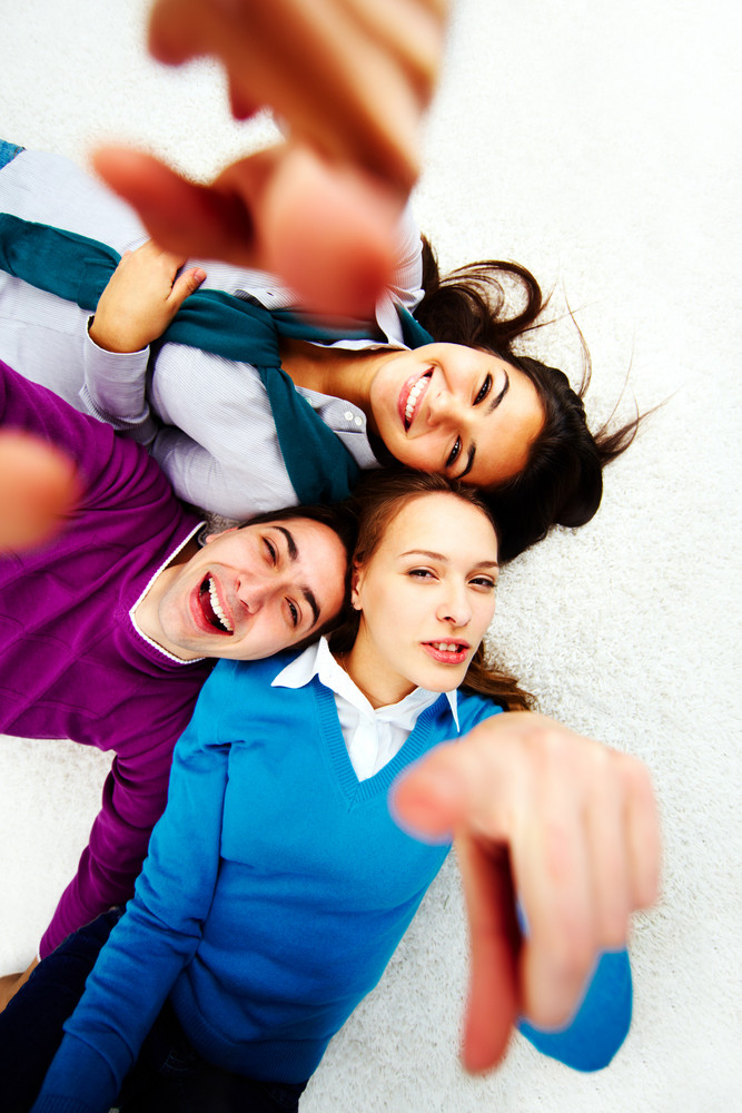 Above Angle Of Teenage Friends Pointing And Looking At Camera