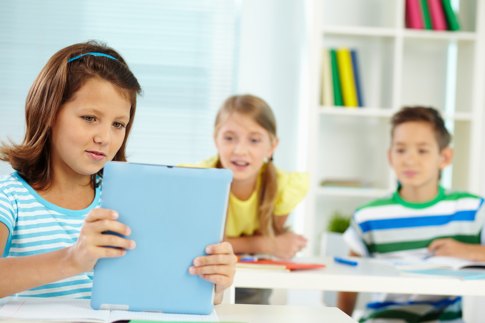 Portrait Of Lovely Girl At Workplace Holding Digital Tablet With Classmates On Background