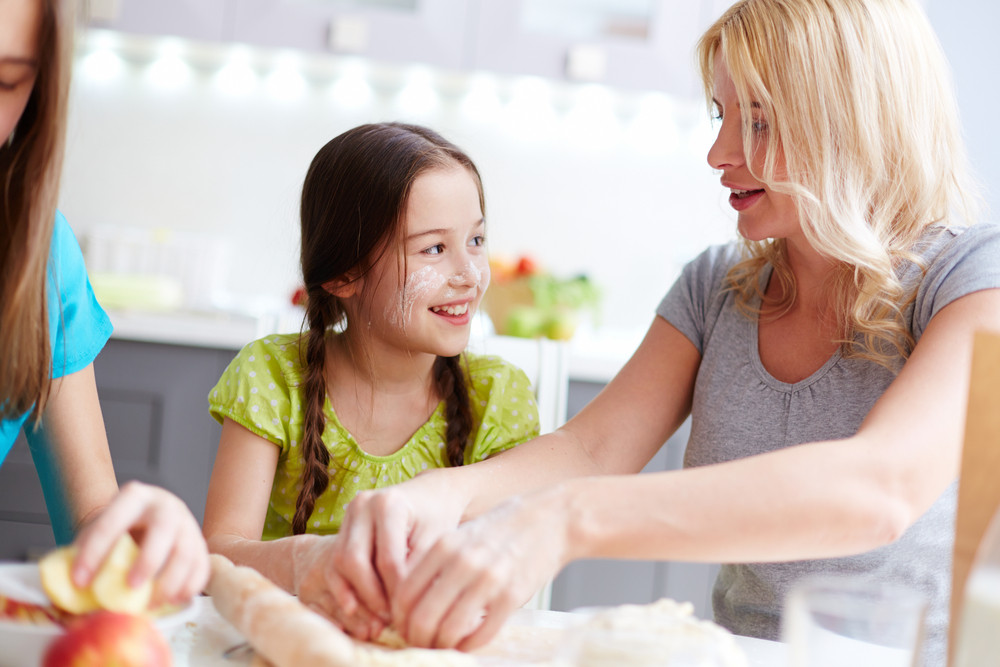 Portrait Of Happy Girl Helping Her Mother To Cook Pastry