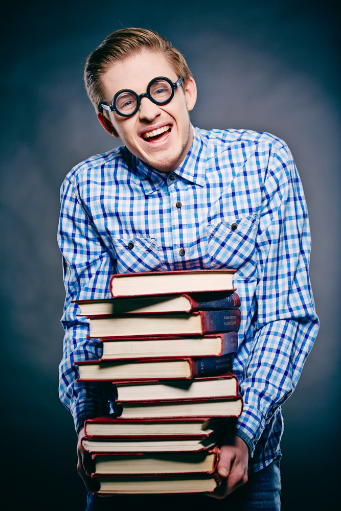 Portrait Of Young Guy In Eyeglasses With Pile Of Books Looking At Camera