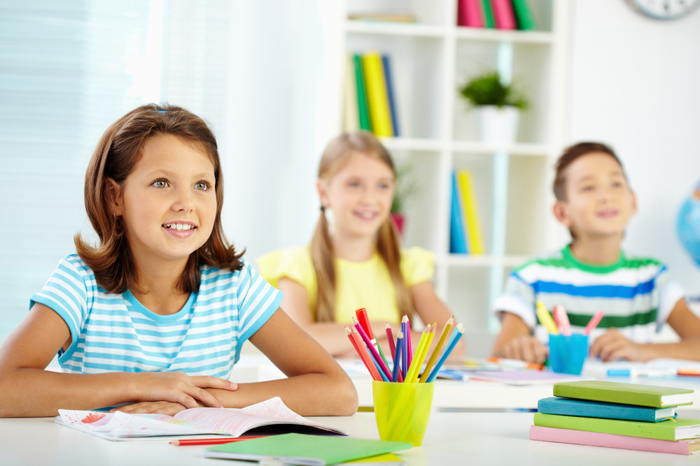 Portrait Of Lovely Girl And Her Two Schoolmates On Background Looking At Something Attentively At Lesson