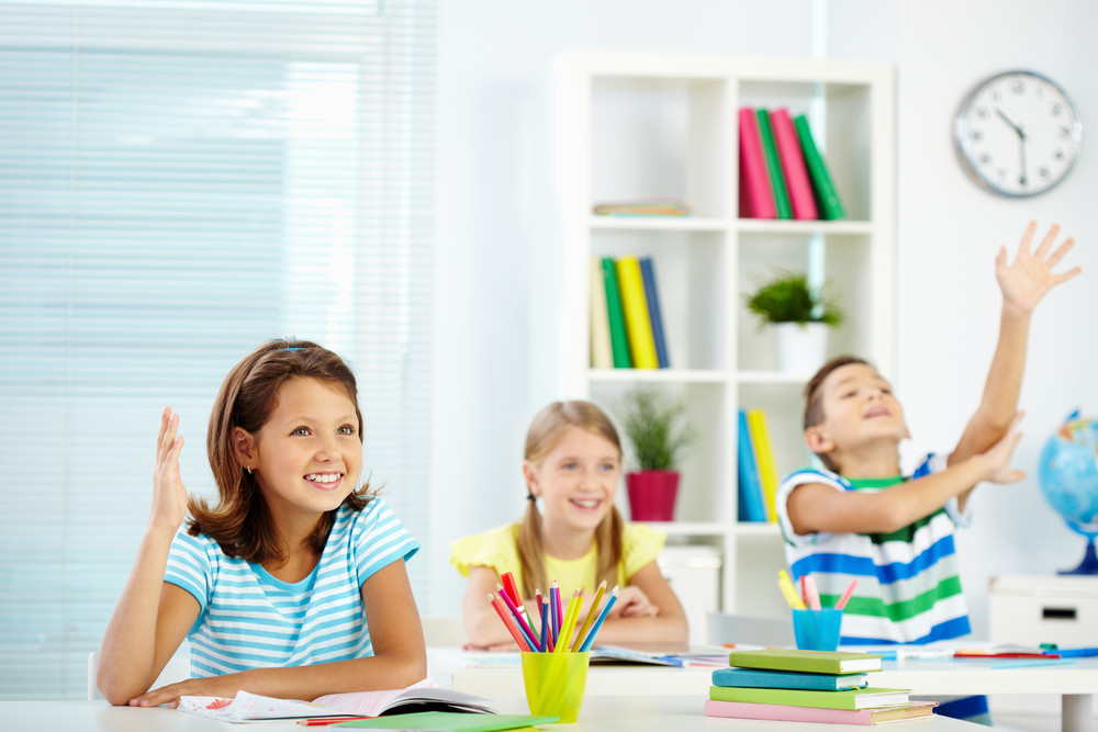 Portrait Of Lovely Girl Raising Hand At Workplace With Happy Classmates Behind