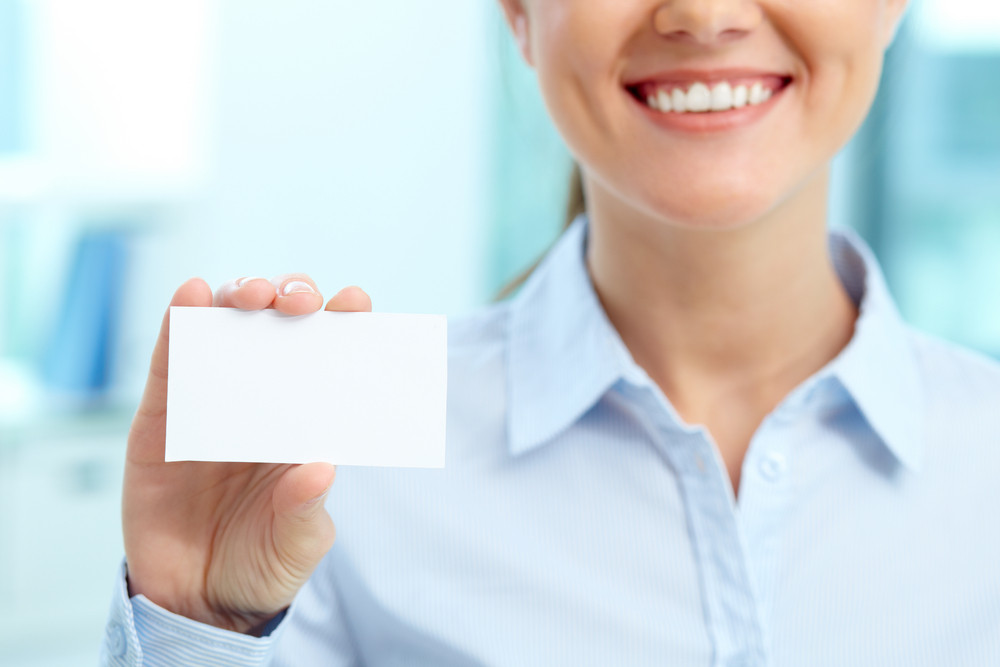 Close-up Of Blank Card Shown By Young Smiling Businesswoman