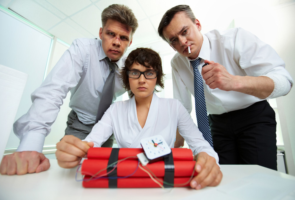 Group Of Businesspeople With Dynamite Looking At Camera In Office