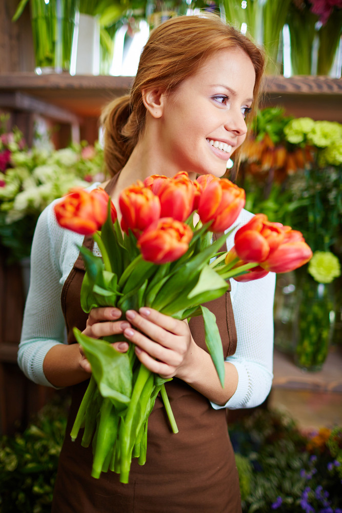 Portrait Of Young Female Florist With Red Tulips