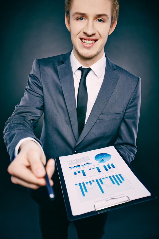 Portrait Of A Young Businessman With Document Offering Pen And Looking At Camera