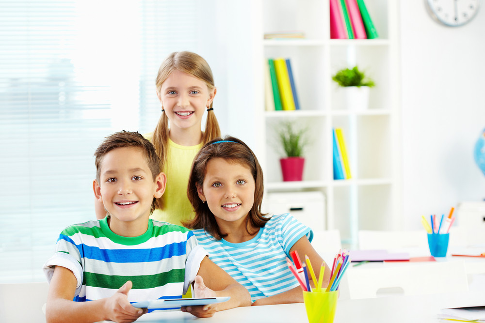 Portrait Of Happy Classmates With Digital Tablet In Classroom