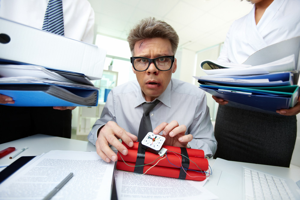 Serious Accountant With Dynamite Being Surrounded By Big Heaps Of Papers