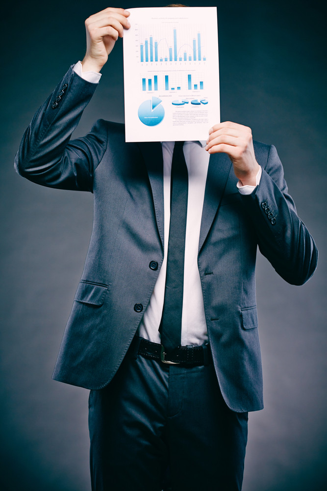 Portrait Of A Young Businessman Holding Document In Front Of His Face