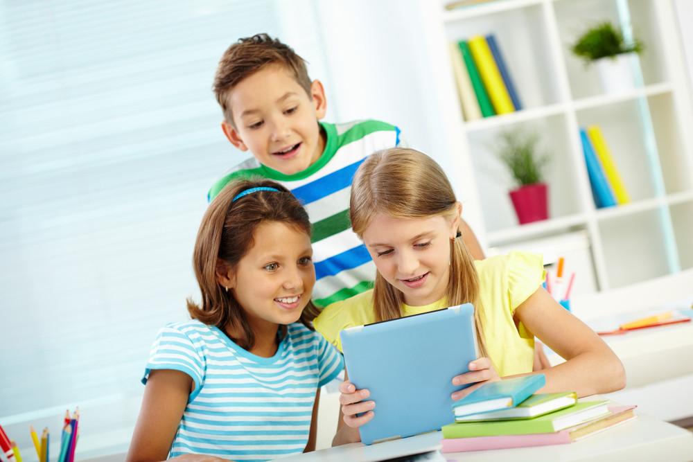 Portrait Of Happy Classmates Looking At Digital Tablet Astonishingly