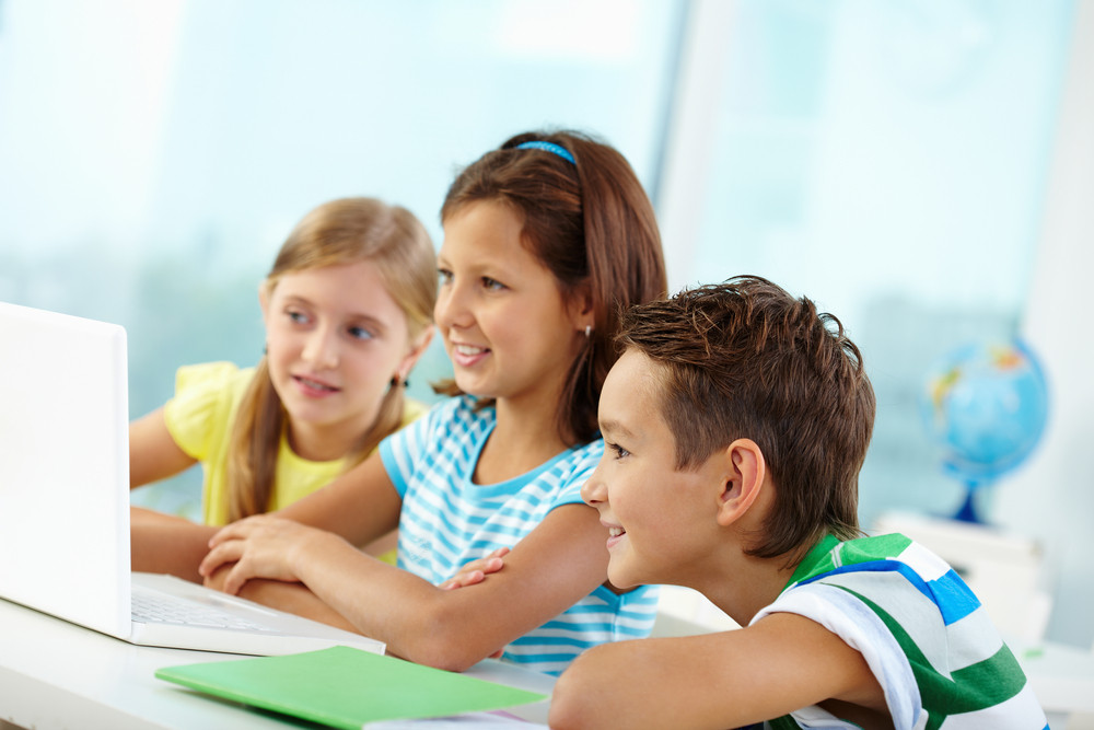 Portrait Of Happy Classmates At Workplace Using Laptop At Lesson