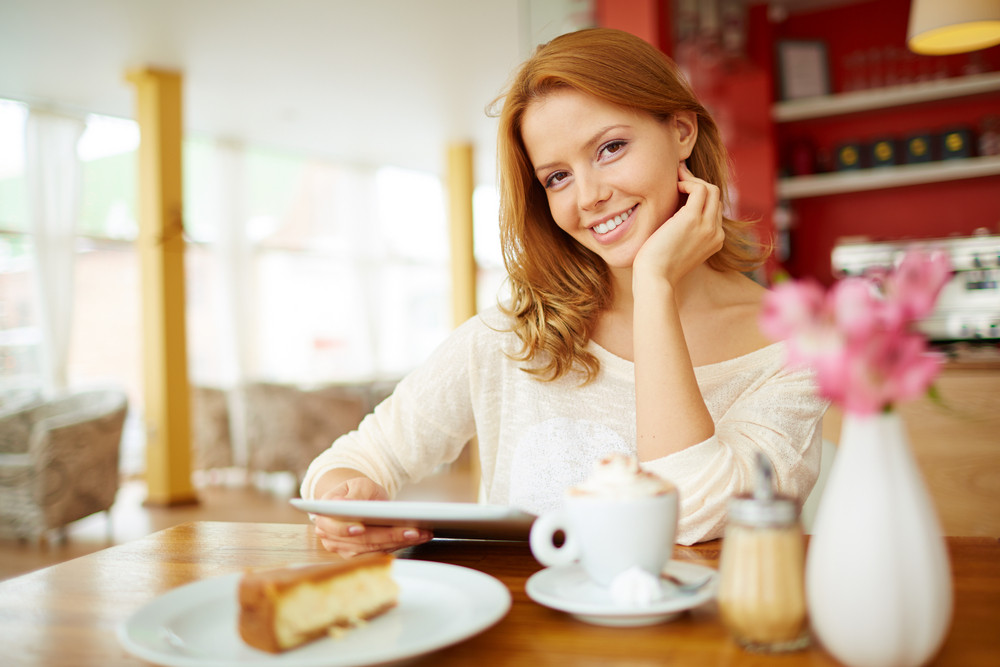 Image Of Young Female With Touchpad Sitting In Cafe And Looking At Camera