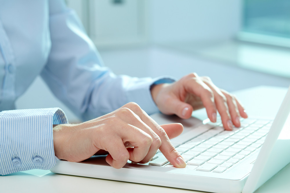 Close-up Of Female Hands Typing On Laptop