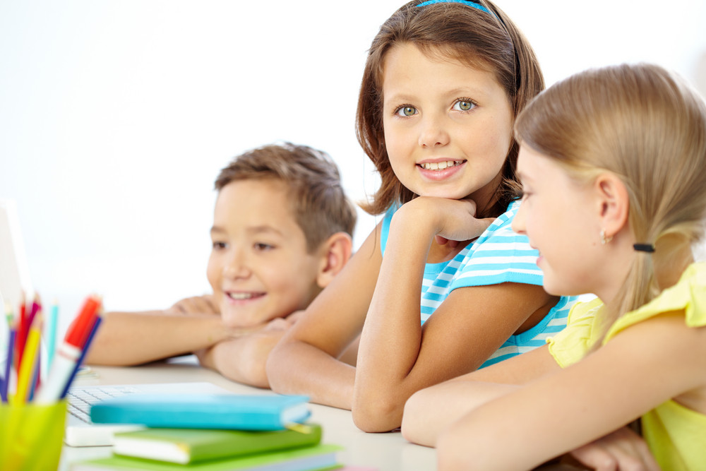 Portrait Of Cute Girl Looking At Camera Among Her Classmates
